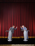 Picture of two men wagging their fingers at each other at a debate on a stage in a theater. The background is a large red velvet theater curtain. The two politicians are facing each other  and pointing with their fingers.